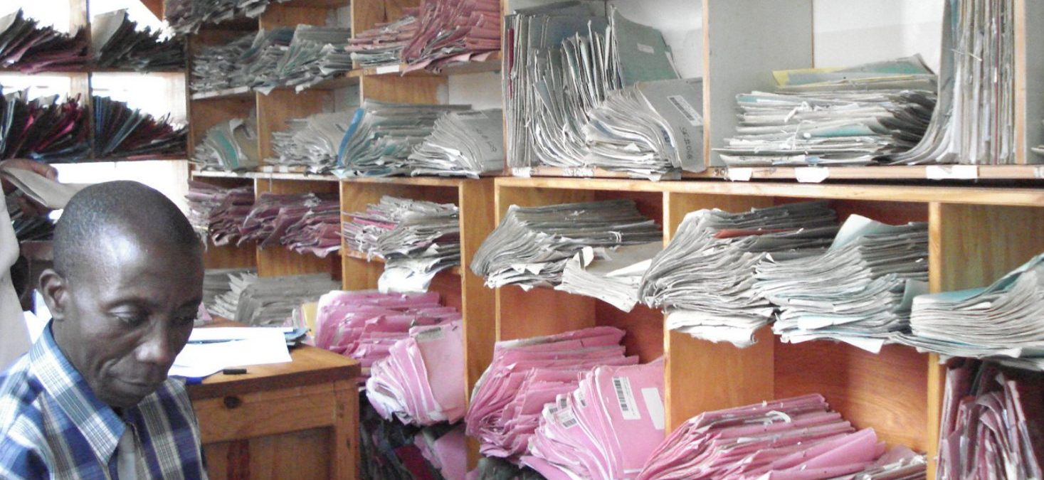 A photograph of hospital patient files on shelves